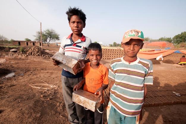 Indiase kinderen van arbeiders die met de hand traditionele bakstenen helpen maken in de steenoven of fabriek