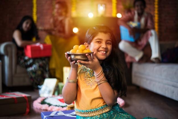 Indiase kinderen vieren diwali, deepawali, bhai dooj of rakhi of raksha bandhan met bloemrangoli, geschenken, diya