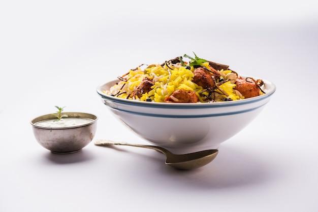 Indiase kip tikka biriyani geserveerd in een kom met yoghurt. selectieve focus