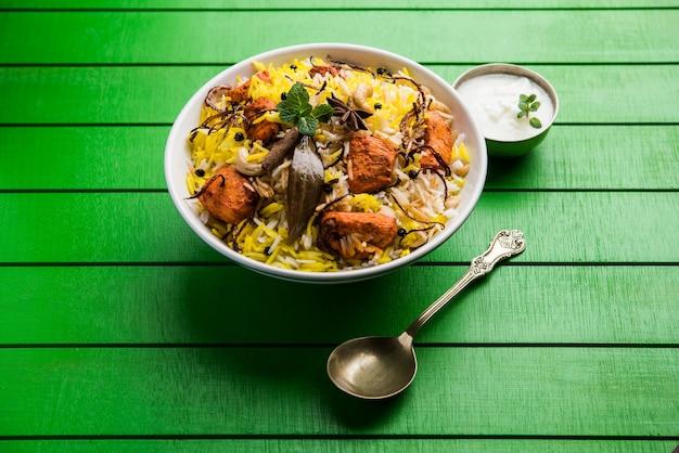 Indiase kip tikka biriyani geserveerd in een kom met yoghurt