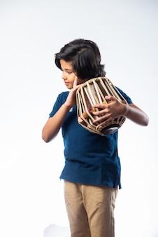 Indiase kleine jongen die tabla-muziekinstrument speelt. het is een hindoestaans klassiek instrument