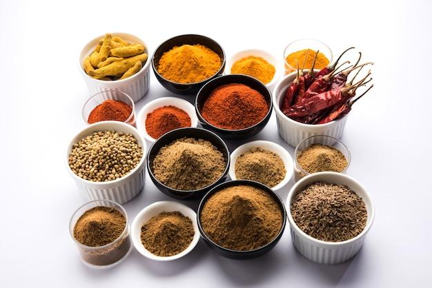 Indiase kleurrijke kruiden. groepsfoto van vier indiase basiskruiden zoals rauwe rode peper, kurkuma, koriander en komijnpoeder. selectieve focus