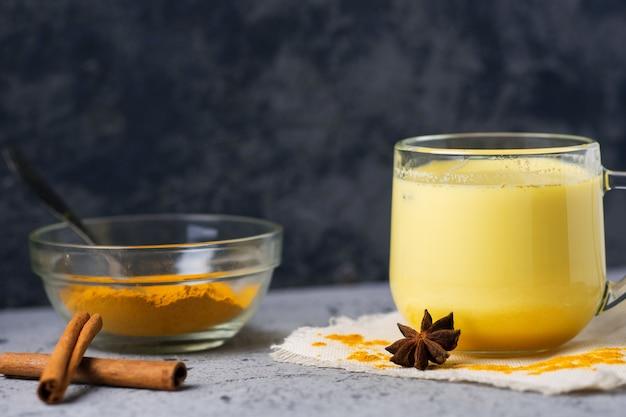 Indiase kruidenkurkuma gouden melk in een mok op een donkere stenen tafel
