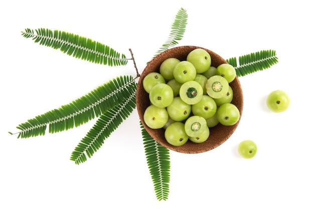 Indiase kruisbes of phyllanthus emblica vruchten en groene bladeren geïsoleerd op een witte achtergrond. bovenaanzicht, plat lag.