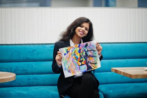 Indiase kunstenaar vrouw draagt formele verf foto, zittend in café.