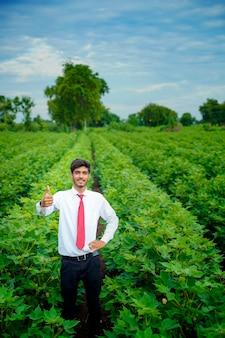 Indiase landbouwingenieur op katoenveld en toont dreun