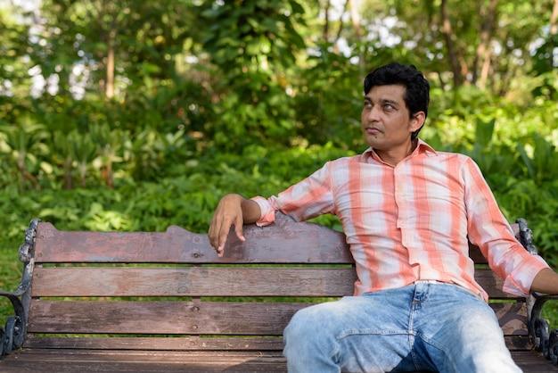Indiase man denken zittend op een houten bankje