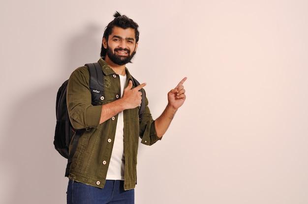 Indiase man die lacht, kijkend naar de camera, wijzende vingers omhoog, gekleed in een jas t-shirt man met rugzak