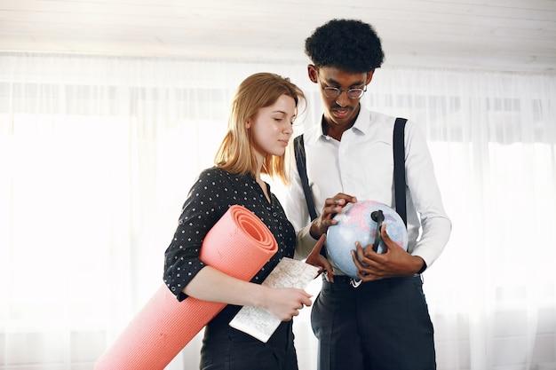Indiase man en europese vrouw met een mat die globe inspecteert. een reisconcept plannen.