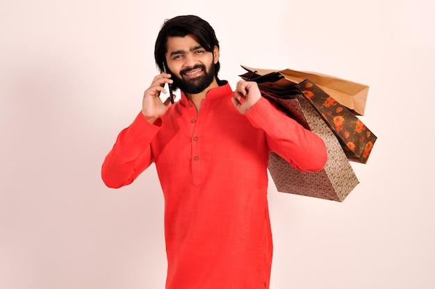 Indiase man met boodschappentassen met kurta die op mobiel praat en glimlacht