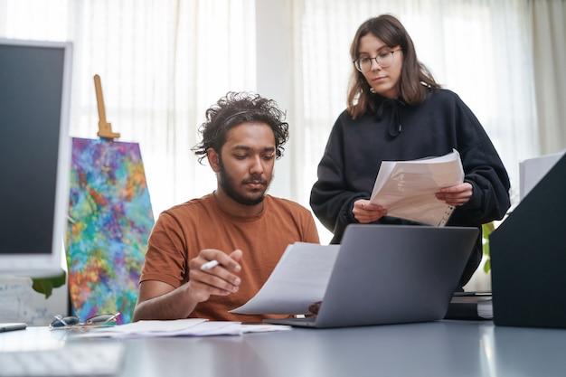 Indiase man met laptop en papieren zit aan tafel en werkt samen met zijn vrouwelijke blanke secretaresse in moderne kantoorruimte.