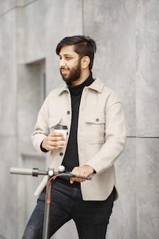Indiase man rijdt op een elektrische scooter. man met koffie.