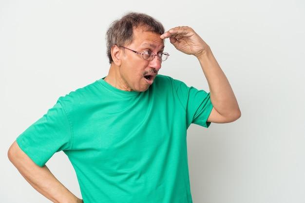 Indiase man van middelbare leeftijd geïsoleerd op een witte achtergrond die ver weg kijkt en de hand op het voorhoofd houdt.