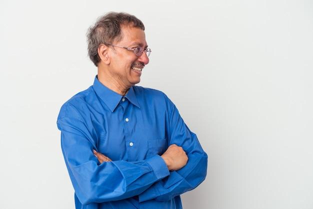Indiase man van middelbare leeftijd geïsoleerd op een witte achtergrond glimlachend zelfverzekerd met gekruiste armen.