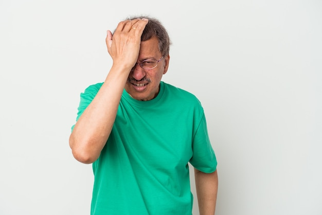 Indiase man van middelbare leeftijd geïsoleerd op een witte achtergrond iets vergeten, voorhoofd met palm slaan en ogen sluiten.
