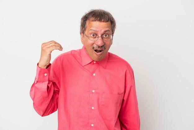 Indiase man van middelbare leeftijd geïsoleerd op een witte achtergrond lachen om iets, mond bedekken met handen.