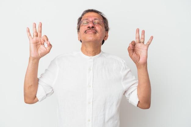 Indiase man van middelbare leeftijd geïsoleerd op een witte achtergrond ontspant na een zware werkdag, ze voert yoga uit.