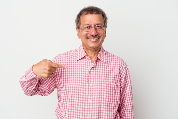 Indiase man van middelbare leeftijd geïsoleerd op een witte achtergrond persoon die met de hand wijst naar een shirt kopieerruimte, trots en zelfverzekerd?