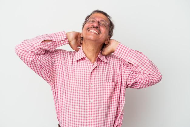 Indiase man van middelbare leeftijd geïsoleerd op een witte achtergrond zelfverzekerd gevoel, met de handen achter het hoofd.