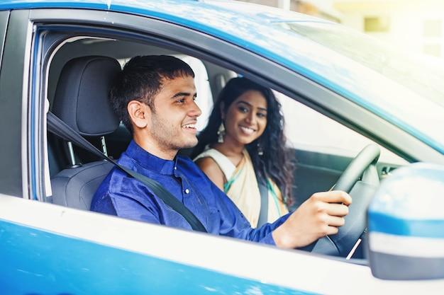 Indiase mannelijke chauffeur die een ritje geeft aan een mooie jonge vrouw