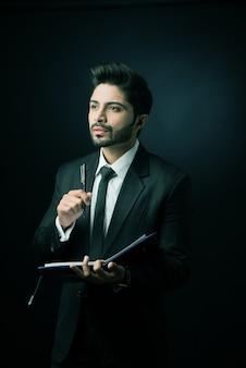 Indiase mannelijke zakenman die in een dagboek schrijft terwijl hij tegen een zwarte achtergrond staat, humeurige verlichting, selectieve focus