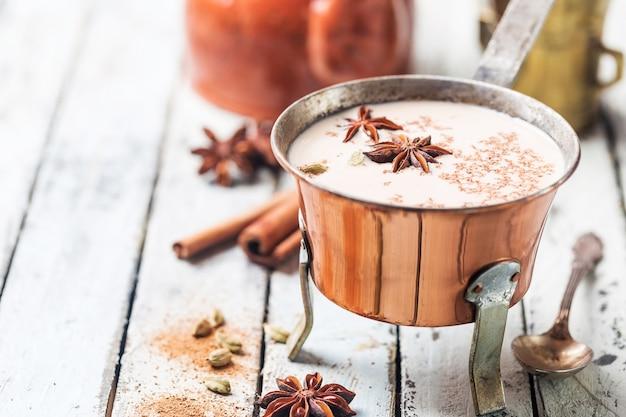 Indiase masala chai thee, gekruide thee met melk in een koperen pot op een witte houten ondergrond