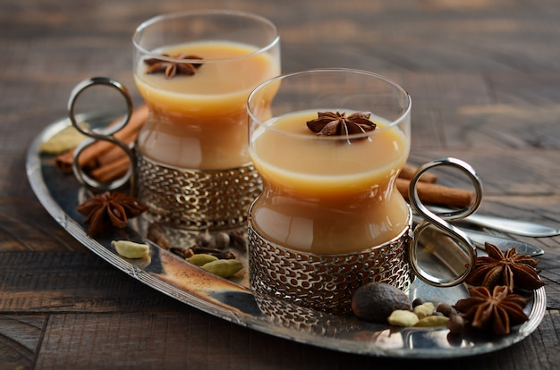 Indiase masala chai thee. gekruide thee met melk in vintage kopjes op de rustieke houten tafel.