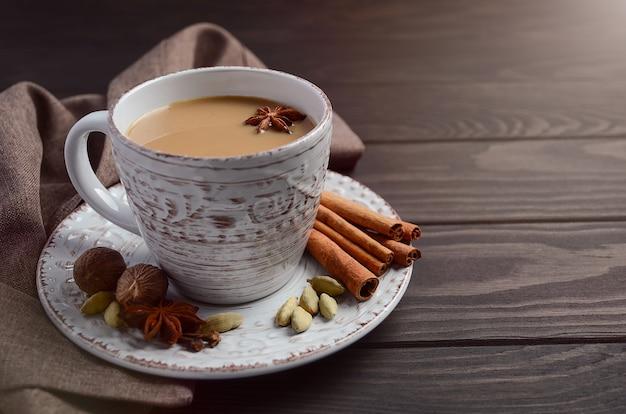 Indiase masala chai thee. gekruide thee met melk op de donkere houten tafel.