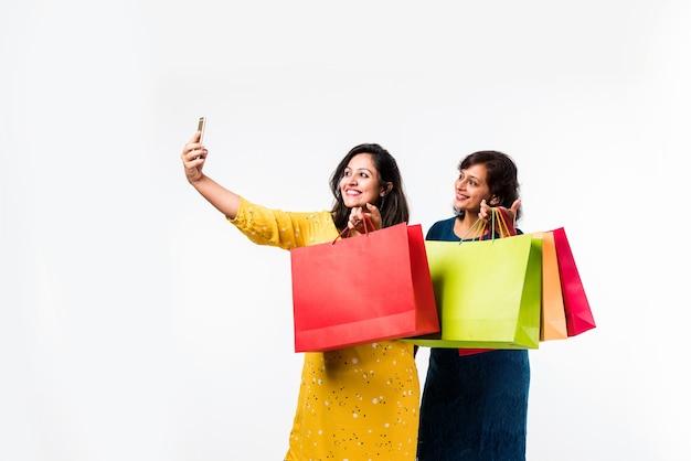 Indiase moeder dochter zusters winkelen met kleurrijke tassen, smartphone controleren of selfie nemen terwijl ze geïsoleerd op een witte achtergrond staan