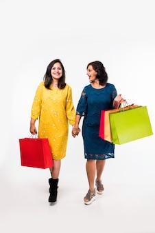 Indiase moeder dochter zusters winkelen met kleurrijke tassen, staande geïsoleerd op witte achtergrond