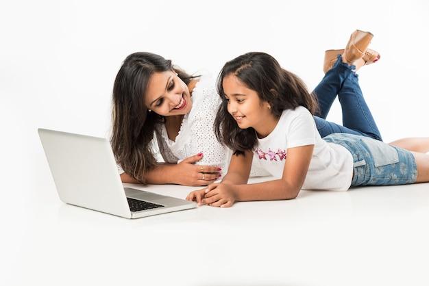 Indiase moeder en dochter liggend op de vloer met boek, laptop of tabletcomputer studeren of voorbereiden verhaal of spelletjes spelen