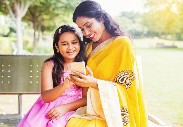 Indiase moeder en dochter met behulp van mobiele telefoon op een bankje in het park