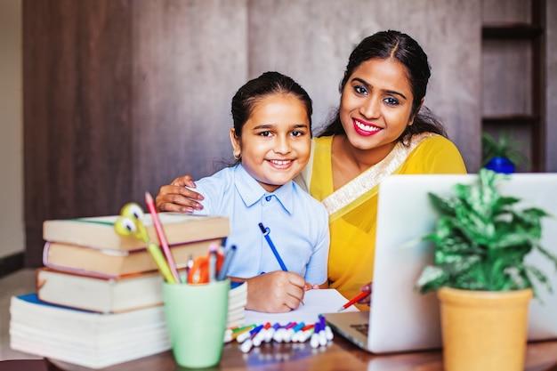 Indiase moeder en haar dochter huiswerk op laptop