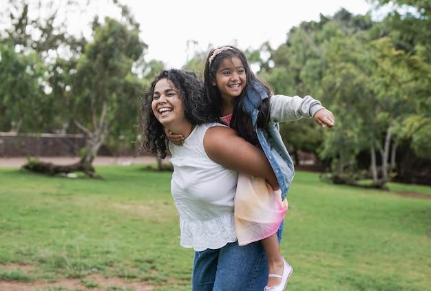 Indiase moeder en schattige dochter hebben speelse tijd in het stadspark - liefde voor moeder en kind