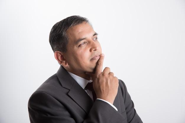 Indiase of aziatische knappe zakenman van middelbare leeftijd in zwart pak die denkt of probeert een oplossing te vinden terwijl hij geïsoleerd staat op een witte achtergrond