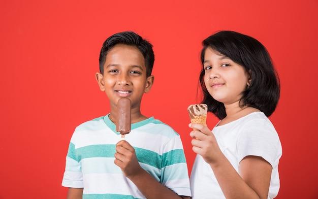 Indiase of aziatische schattige kleine kinderen die ijs of mangoreep of snoep eten. geïsoleerd over kleurrijke achtergrond