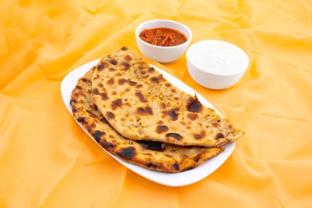 Indiase ontbijtschotel aloo paratha geserveerd met wrongel en augurk