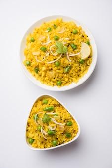 Indiase ontbijtschotel poha ook bekend als pohe of aalu poha bestaande uit geklopte rijst of afgeplatte rijst. de rijstvlokken zijn licht gebakken in olie met kruiden geserveerd met hete thee
