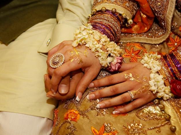 Indiase pakistaanse bruid en bruidegom zitten en houden elkaars hand vast op henna mehndi-feestje van dichtbij