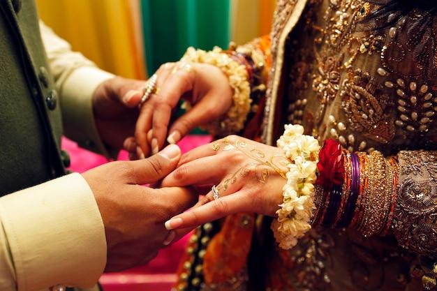 Indiase pakistaanse verloofde paar handen met sieraden, henna en bloemen tijdens henna party close-up