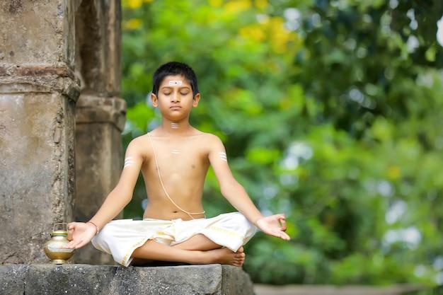 Indiase priester kind doet yoga in het park