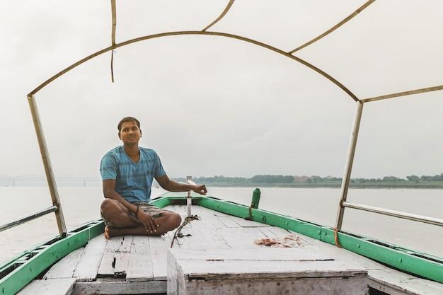 Indiase roeier zittend op de boot die drijvend over de rivier de ganges (ganga) in varanasi, uttar pradesh, india.