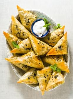 Indiase samosa gemaakt met filodeeg met pittige aardappelen en groenten, geserveerd met yoghurt, munt en citroen. close-up voor reclame