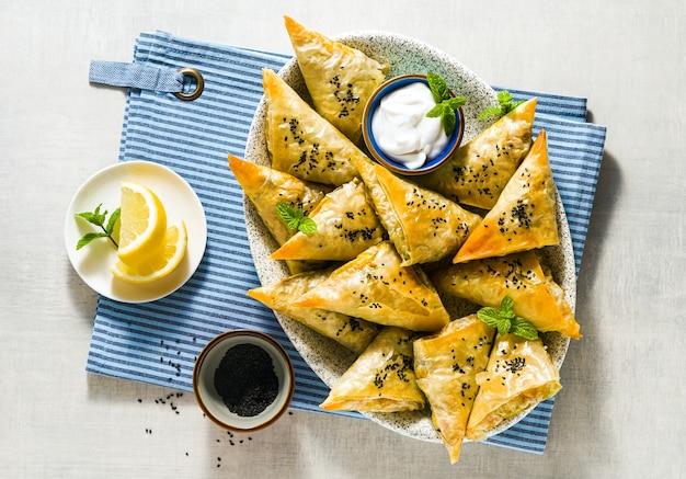 Indiase samosa gemaakt met filodeeg met pittige aardappelen en groenten, geserveerd met yoghurt, munt en citroen op een blauw servet in een restaurant