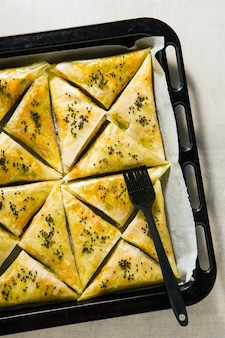 Indiase samosa gemaakt met filodeeg met pittige aardappelen en groenten op een bakplaat, klaar om gebakken te worden in de oven met zwarte sesamzaadjes
