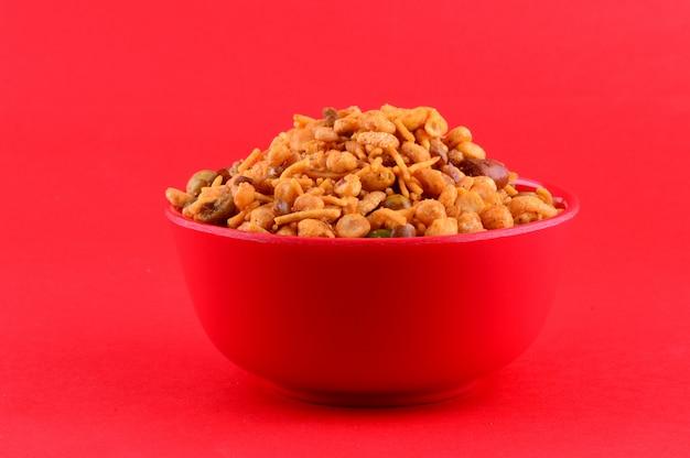 Indiase snacks: mengsel (geroosterde noten met masala van zoutpeper, peulvruchten, channa masala dal, groene erwten) in rode kom op rode achtergrond