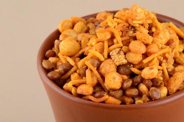 Indiase snacks: mengsel (geroosterde noten met masala van zoutpeper, peulvruchten, groene dala erwten masala) in blauwe kom in