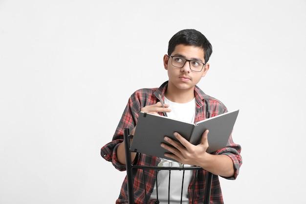 Indiase student die enkele aantekeningen in notitieboekje op witte muur schrijft