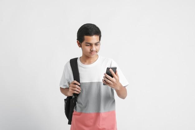 Indiase student met behulp van smartphone op witte muur