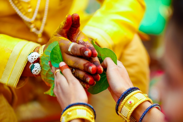 Indiase traditionele huwelijksbruidegom hand in haldi-ceremonie